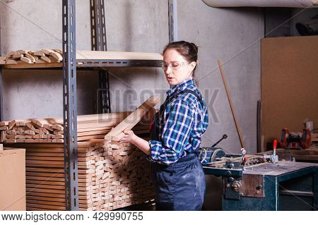 Female Apprentice Checking Wooden Plank At Carpentry Workshop