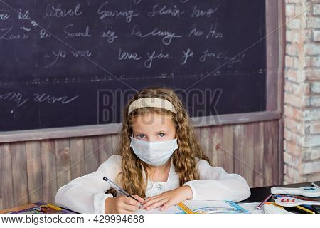 Girl With Face Mask, Back At School After Covid-19 Quarantine And Lockdown. School Girl Writing In E