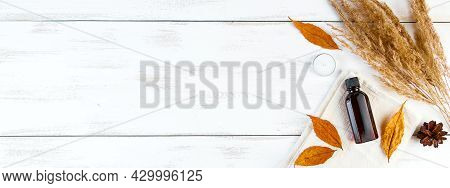 Autumn Skin Care Concept. Bottle Of Pine Essential Oil On A White Wooden Background. Aromatherapy An