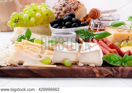 Cheese Platter With Assorted Cheese, Sausage, Jam, Black Olives, Pine Nuts And Grapes Topped With Ba