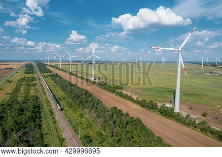 Aerial View Of Wind Power Turbine Is A Popular Sustainable, Renewable Energy Source On Beautiful Clo