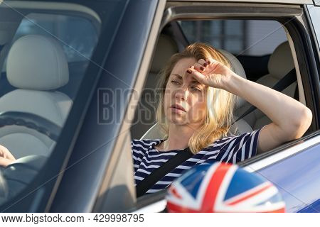 Tired Frustrated Woman Driver Looking At Traffic Jam Through Windshield Of Modern Car. Sad Female Of