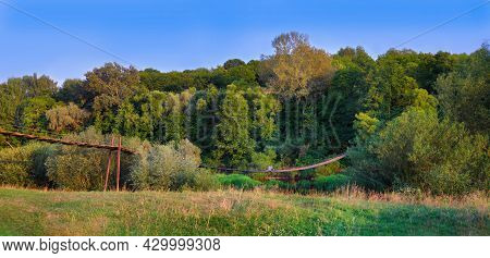 Wooden Suspension Bridge Over A Quiet River At Sunset. The Figure Of A Man Is Sitting On A Suspensio