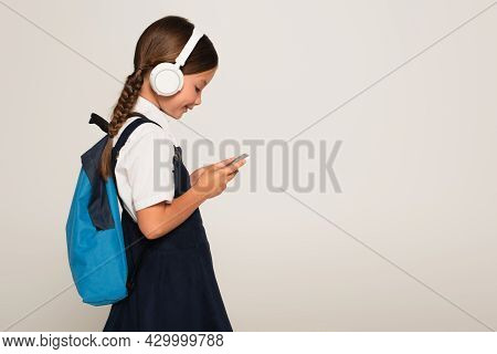 Side View Of Cheerful Schoolkid In Headphones Using Smartphone Isolated On Grey
