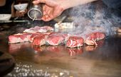 Japanese chef doing his magic on the hot plate at the Teppanyaki restaurant.Grilling scotch fillet poster