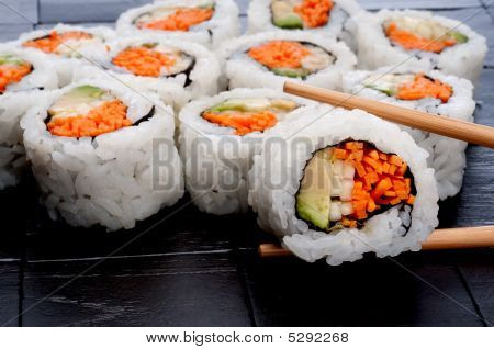 Chopsticks Holding Sushi In Front Of More Sushi