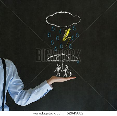 Insurance Businessman Holding Out Hand Protecting Family From Natural Disaster On Blackboard Backgro