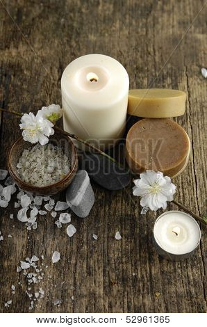 white flower with candle, stones ,sopa, salt on driftwood texture