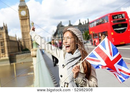 London - happy tourist holding British UK flag by Big Ben and red double decker bus. Excited girl sightseeing travel on Westminster Bridge, London, England, United Kingdom. Multiracial Asian Caucasian