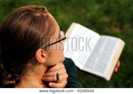 Student Reading A Bible In A Public Park