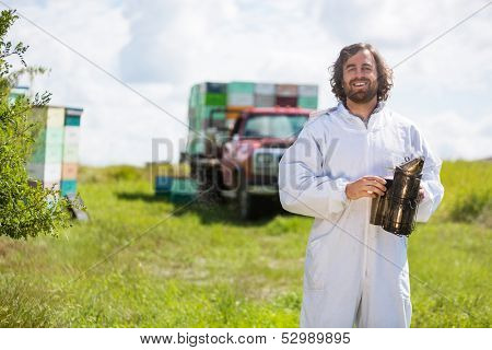 Portrait of happy beekeeper in protective clothing holding smoker while standing at apiary
