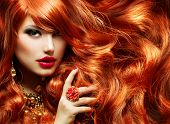 Long Curly Red Hair. Fashion Woman Portrait. Beauty Model Girl with Luxurious Hair, Make up and Accessories. Hairstyle. Wavy Hair Extensions Concept. Holiday Makeup. Smoky eyes and Red lipstick poster