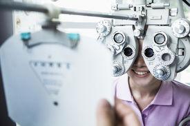 Close-up of optometrist doing eye exam on young woman