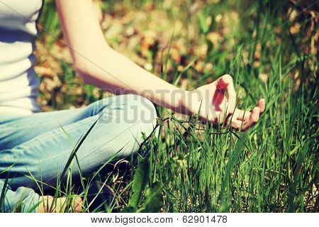 Young woman during relaxation and meditation in park meditation session. Frame shows half of body.