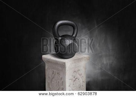 Cast iron kettlebell on a pedestal.