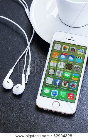 New Apple Iphone 5s in gold color with earphones.