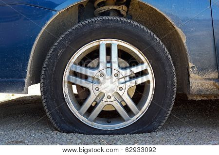 Flat Car Tire On Gravel Road