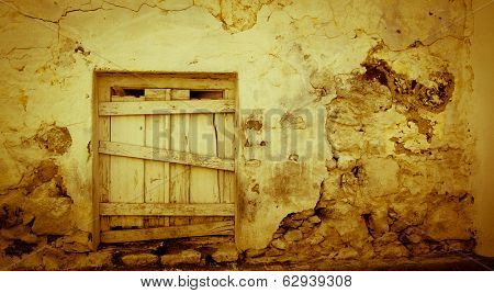 Little wooden door on a grungy yellow wall