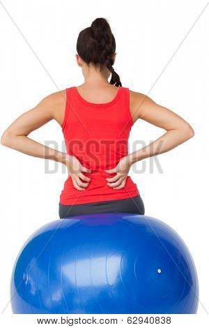 Rear view of a fit young woman sitting on exercise ball over white background