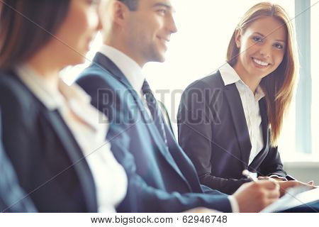 Smiling businesswoman looking at camera at seminar with her colleagues near by