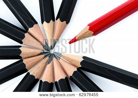 One Red Pencil Standing Out From The Circle Of Black Pencils