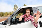 Car driver showing car keys and thumbs up happy. Young man holding car keys for new car. Rental cars or drivers licence concept with male driving in beautiful nature on road trip. poster