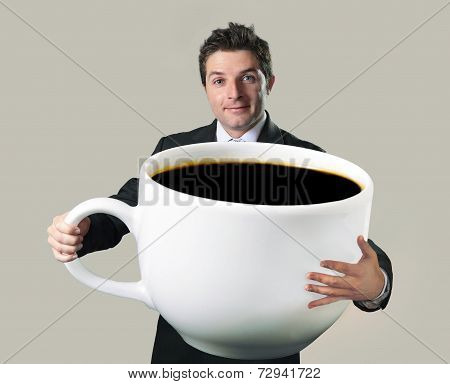 young happy business man holding a funny huge and oversized cup of black coffee in caffeine addiction concept isolated on even background poster