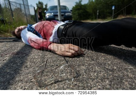 Bleeding man lying on the street after car accident poster