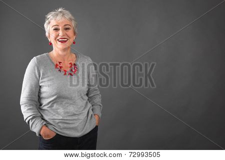 Happy senior woman standing hands in pockets