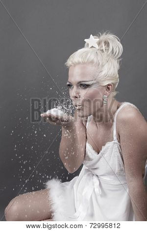 Attractive woman blowing snow in white babydoll
