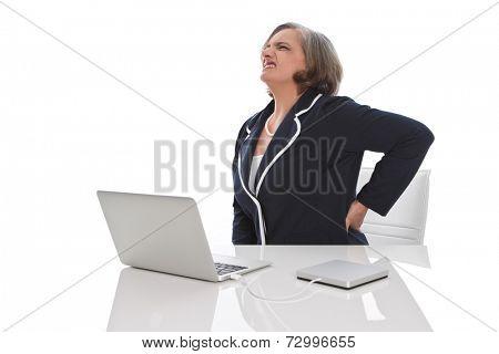 Elderly business woman sitting at desk having backache.