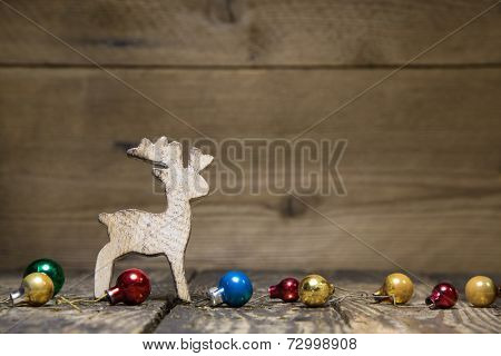 Wooden elk or reindeer on a old rustic country style, background with old christmas balls for a natural greeting or gift card