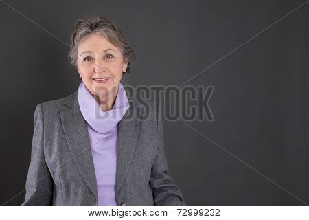 Smart senior woman with grey hair on grey background