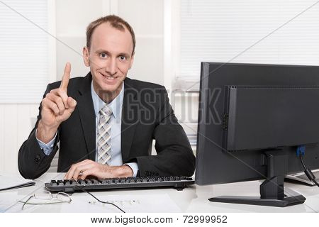 Portrait of a smiling businessman showing his index finger sitting at desk with computer in suit and tie