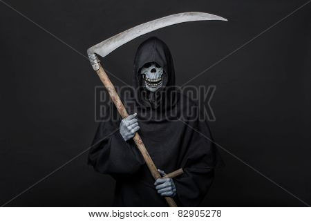 Death with scythe standing in the dark. Halloween