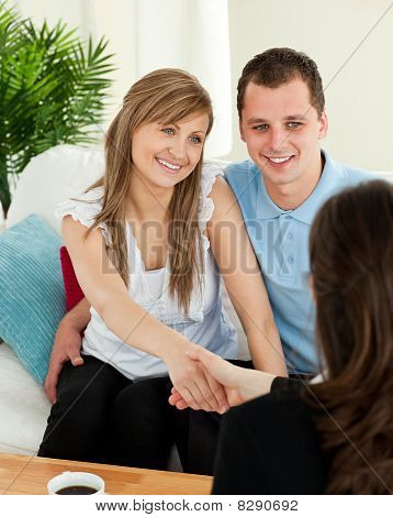 Happy Couple Concluding A Contract With A Female Dealer