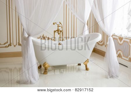 White Luxurious Bath With Golden Legs At Bathroom