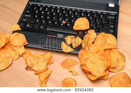 Close Up Of Open Laptop With Chips Scattered On Keyboard