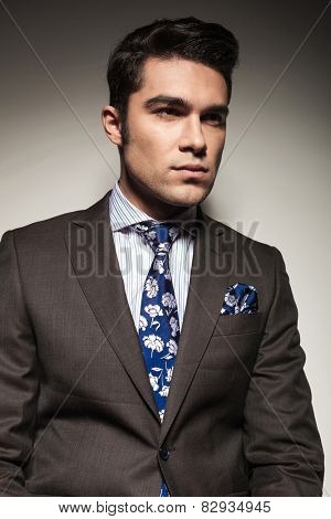 Close up picture of a young business lookin away from the camera, on grey studio background.