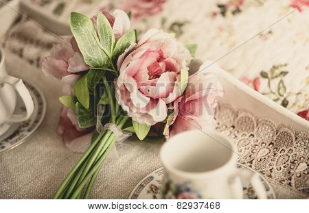 Retro Styled Photo Of Pink Flowers Lying On Tray With Teacups