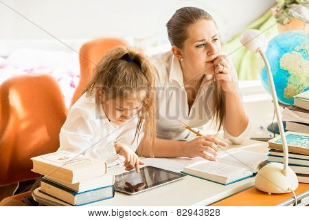 Mother Sitting Next To Daughter Doing Homework