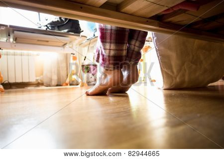 Photo From Under The Bed On Barefoot Woman In Pajamas
