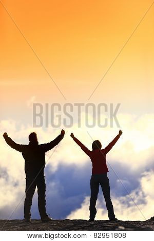 Success, life achievement, goal accomplishment concept with hiking people cheering and celebrating of joy with arms raised outstretched up in the sky outside on mountain summit. poster