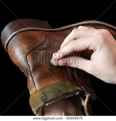 The shoemaker puts shoe polish on black background