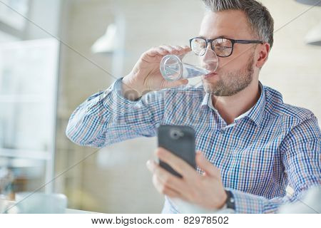 Businessman in casualwear drinking water while reading sms or dialing number on cellphone poster