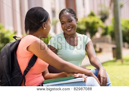 young college girl friends talking outside on campus