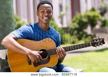 cheerful young african american man playing guitar outdoors