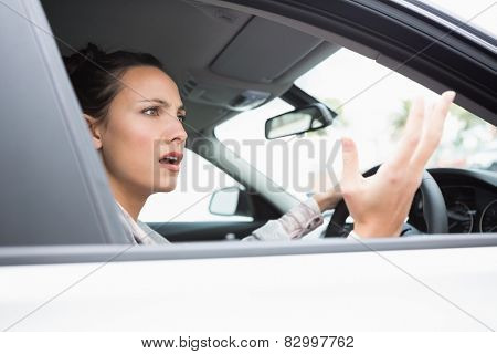 Pretty businesswoman experiencing road rage in her car