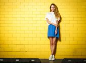 Full Length Portrait of Trendy Hipster Girl Standing at the Yellow Brick Wall Background. Urban Fashion Concept. Copy Space. poster