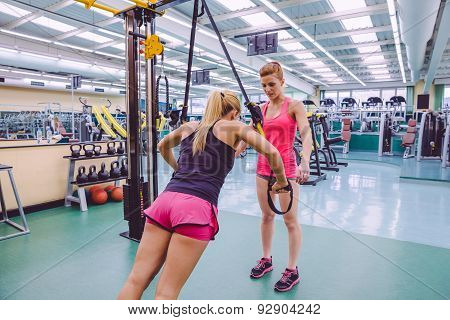Female personal trainer teaching to woman in a hard suspension training with fitness straps on a fitness center poster